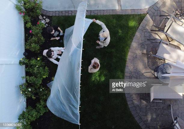 An aerial view of Olivia and James Grant greeting their grandparents Mary Grace and Domenik Sileo through a plastic drop cloth hung up on a homemade...