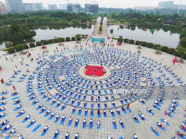 An aerial view of over 1000 yoga enthusiasts performing yoga exercises during a mass physical fitness activity at a park on May 27 2018 in Fengxian...