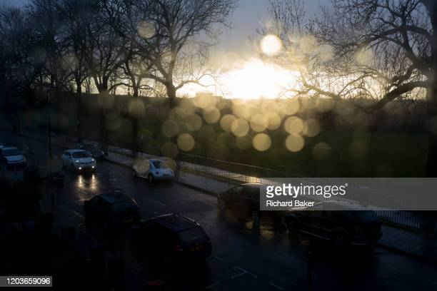 An aerial view of parked cars on a south London street flooded by sunlight after heavy rainfall with outoffocus spots of water on the glass of a...