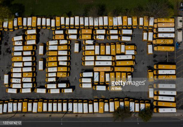 An aerial view of parked school buses in a parking lot bus depot on April 25, 2020 in Freeport, New York. Freeport schools have been closed since...