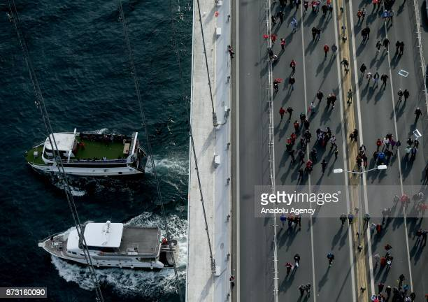 An aerial view of participants competing as two boats pass Bosphorus during Vodafone 39th Istanbul Marathon at The 15 July Martyrs Bridge in Istanbul...
