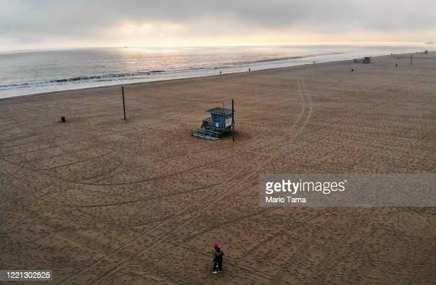 An aerial view of people embracing before sunset on a nearly empty Venice Beach which remains closed along with all other Los Angeles County beaches...