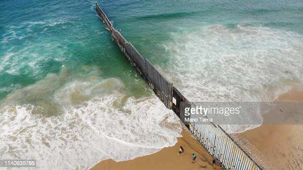 An aerial view of people standing on the Mexican side of the USMexico border on the beach with the border barrier at right on April 5 2019 in Tijuana...