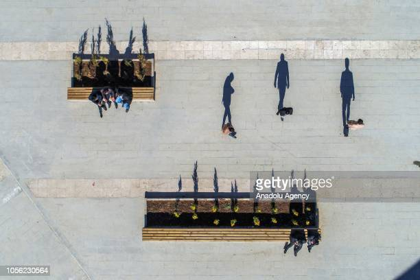 An aerial view of people's shadows reflecting on the ground along with people sitting on benches at a pedestrian zone in Turkey's eastern Van...