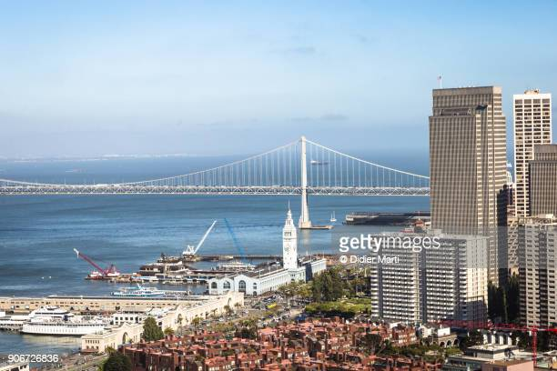 An aerial view of San Francisco Embarcadero with the iconic ferry terminal building, right next to the financial district, and the San Francisco Oakland Bay bridge