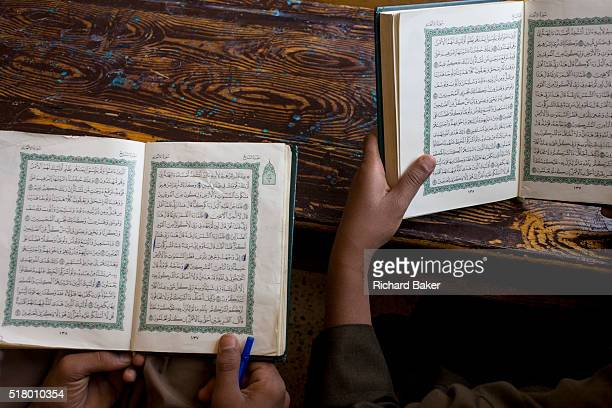 An aerial view of schoolboys reading Arabic verses from the Koran in a classroom at the Islamic Koom alBourit Institute for Boys in the village of...