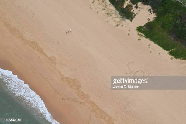 An aerial view of 'SOS' written in the sand at Curl Curl beach on December 21, 2020 in Sydney, Australia. Sydney's northern beaches is on lockdown,...