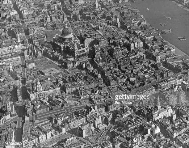 An aerial view of St Paul's Cathedral in the City of London with the River Thames at the top right and Farringdon Street in the foreground circa 1955