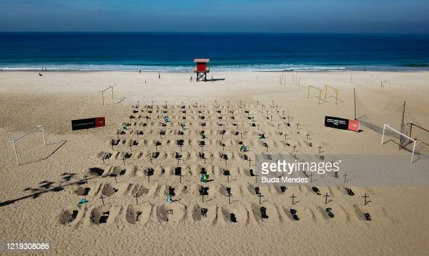An aerial view of symbolic graves digged by protesters from the NGO 'Rio De Paz' as a sign of protest in Copacabana beach on June 11, 2020 in Rio de...