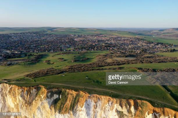 An aerial view of the 15th, 16th, and 17th holes perched on top of the cliffs with the town of Seaford behind at the Seaford Head Golf Course on...