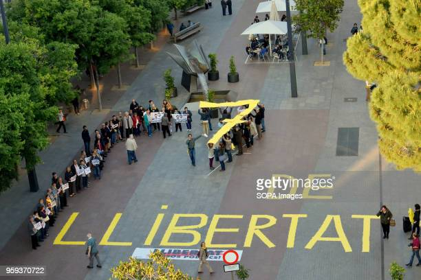 An aerial view of the demonstration with protesters forming a '7' with yellow placards Around fifty people gathered in L'Hospitalet City to demand...