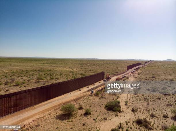 an aerial view of the international border wall with portions still under construction - chihuahua desert stock pictures, royalty-free photos & images