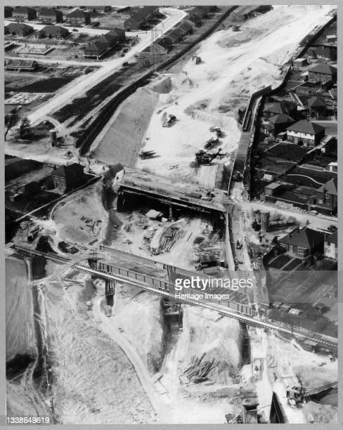 An aerial view of the London to Yorkshire Motorway under construction, showing the Luton to Dunstable railway bridge in the foreground and the bridge...