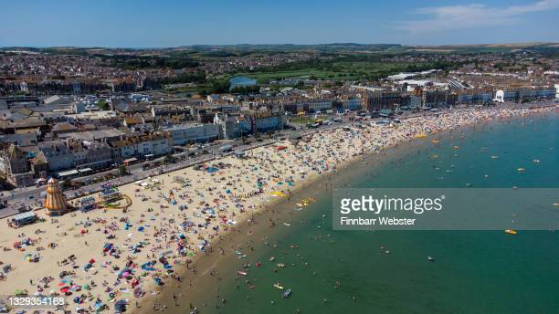 An aerial view of the packed beach on July 18, 2021 in Weymouth, England. A heat-heath warning has been issued for England this weekend, with...