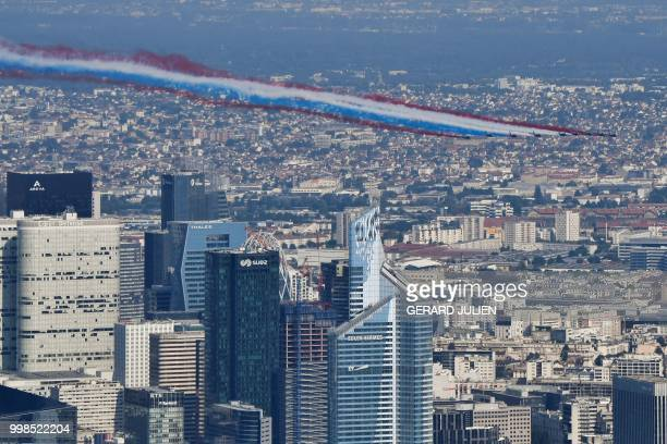 TOPSHOT An aerial view of the Patrouille de France Alpha Jet aircrafts flying over the city during the annual Bastille Day military parade on the...