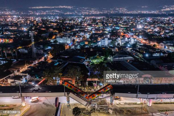 An aerial view of the scene after an elevated section of metro track in Mexico City, carrying train cars with passengers, collapsed onto a busy road...