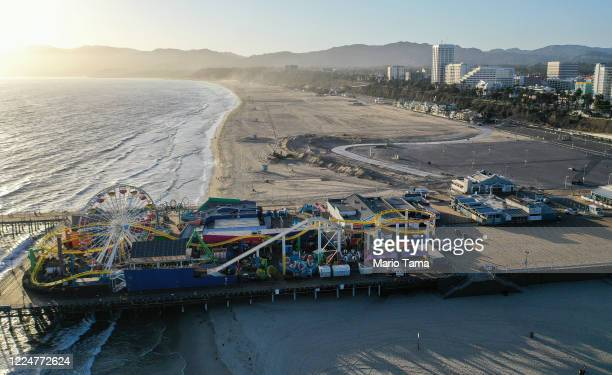 An aerial view of the shuttered Santa Monica Pier on Santa Monica Beach before sunset, on the day Los Angeles County reopened its beaches which had...