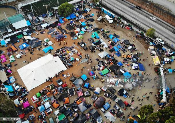 An aerial view of the temporary shelter set up for members of the 'migrant caravan' with a section of the USMexico border barrier visible on November...