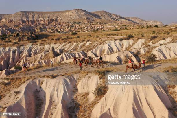 An aerial view of tourists riding camels while touring the fairy chimneys at the historical Cappadocia region, located in Central Anatolia's Nevsehir...