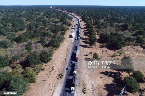 An aerial view of trucks waiting in the long queue to cross the river over the Kazungula bridge in Kazungula, Botswana, on May 10, 2021. - A new road...