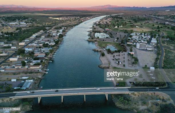 An aerial view of vehicles crossing over a bridge spanning the Colorado River, the border between Needles, California and Mohave Valley, Arizona ,...