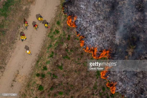 An aerial view of volunteer firefighters practicing with a live burn during a wildfire training course on May 8, 2021 in Brewster, Washington. New...