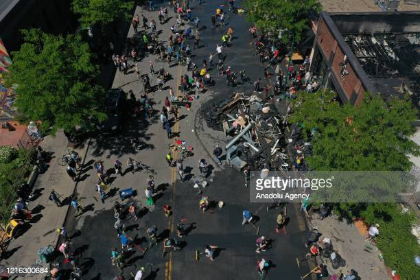 An aerial view of volunteers cleaning trash and debris after riots over the death of an unarmed black man George Floyd who was killed as he was...