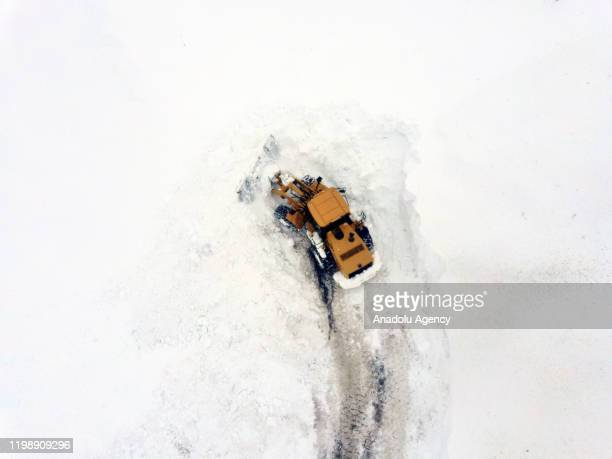 An aerial view of workers using a heavy machine to clear huge masses of snow from the streets in Turkey's eastern Mus province on February 06 2020...