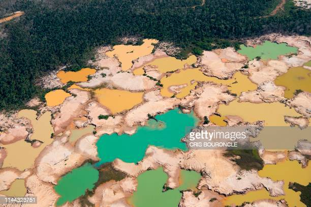 An aerial view over a chemically deforested area of the Amazon jungle caused by illegal mining activities in the river basin of the Madre de Dios...