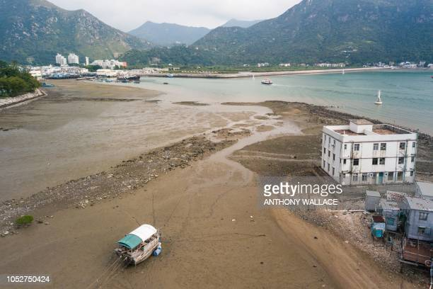 An aerial view shows a boat resting on a bed of sand during low tide in the fishing village of Tai O in Hong Kong on October 22, 2018.