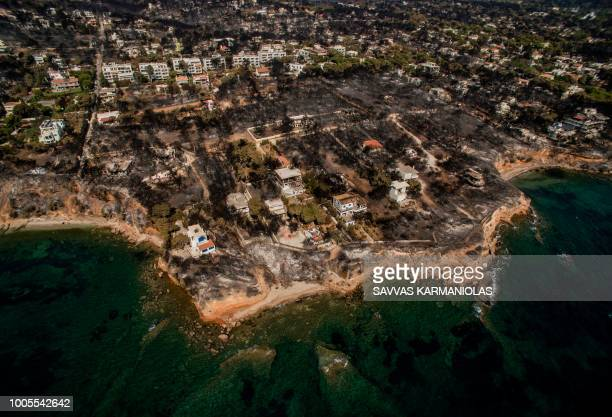 TOPSHOT An aerial view shows a burnt area following a wildfire in the village of Mati near Athens on July 26 2018 Greece was counting the cost on...