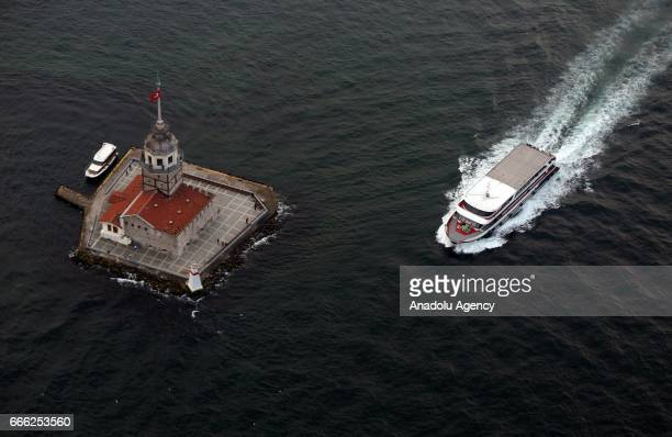 An aerial view shows a ferry passes by The Maiden's Tower also known as Leander's Tower on Bosphorus in Istanbul Turkey on April 08 2017 Since the...