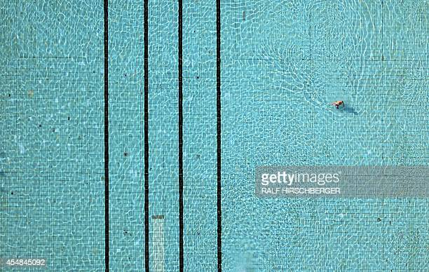 An aerial view shows a man in a swimming pool in Kleinmachnow eastern Germany on September 7 2014 AFP PHOTO / DPA/ RALF HIRSCHBERGER GERMANY OUT