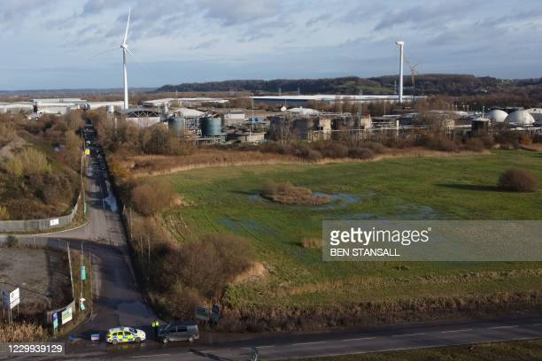 An aerial view shows a police vehicle forming cordon with a damaged silo seen in the background at a waste water treatment plant in Avonmouth, near...