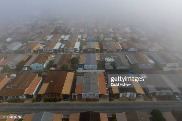 An aerial view shows a quiet neighborhood on a foggy morning as residents continue to stay at home to fight the coronavirus pandemic on April 26 2020...