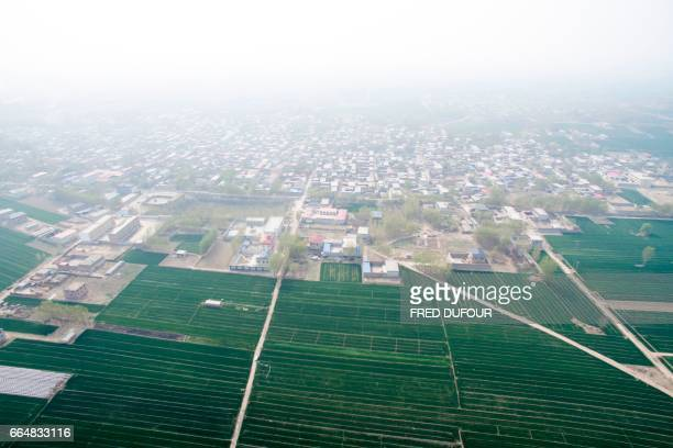 An aerial view shows agricultural fields next to an urban area in Anxin in China's Hebei province on April 5 2017 China will create a new special...