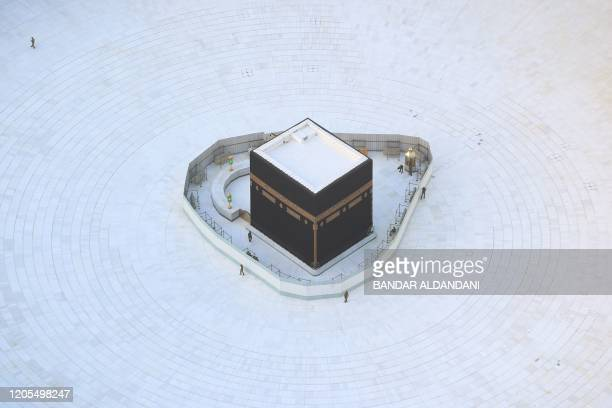 An aerial view shows an empty whitetiled area surrounding the Kaaba in Mecca's Grand Mosque on March 6 2020 An eerie emptiness enveloped the sacred...
