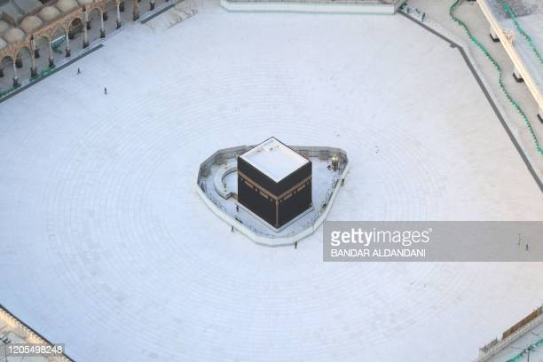 An aerial view shows an empty white-tiled area surrounding the Kaaba in Mecca's Grand Mosque, on March 6, 2020. - An eerie emptiness enveloped the...