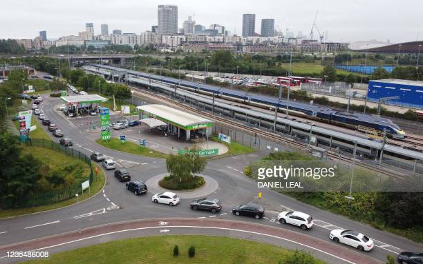 An aerial view shows customers queueing in their cars to access an Asda petrol station in east London on September 25, 2021. - The UK government is...