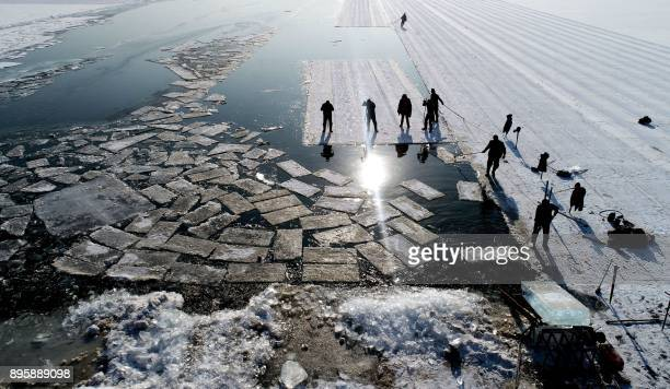 TOPSHOT An aerial view shows floating ice blocks cut from the frozen surface of Xiuhu lake in Shenyang northeastern China's Liaoning province on...