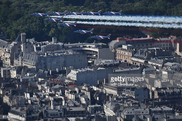 TOPSHOT An aerial view shows French AlphaJet aircrafts of the Patrouille de France flying over the city of Paris during the annual Bastille Day...