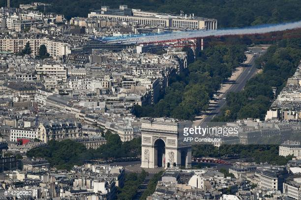 An aerial view shows French AlphaJet aircrafts of the Patrouille de France flying over The Arc de Triomphe on the Champs Elysees Avenue in Paris on...