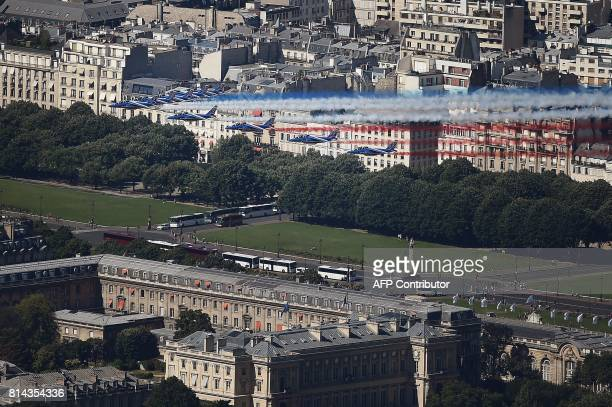 An aerial view shows French AlphaJet aircrafts of the Patrouille de France flying over the city during the annual Bastille Day military parade on the...