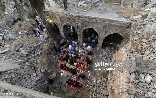 An aerial view shows Iraqi worshippers taking part in the Eid Al-Fitr prayer in the Old City of Mosul, in the courtyard of the damaged Umayad mosque,...