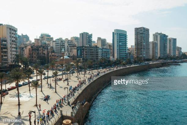 An aerial view shows Lebanese protesters holding hands to form a human chain along the coast from north to south as a symbol of unity during ongoing...