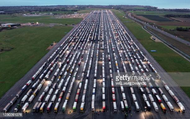 An aerial view shows lines of freight lorries and heavy goods vehicles parked on the tarmac at Manston Airport near Ramsgate, south east England on...