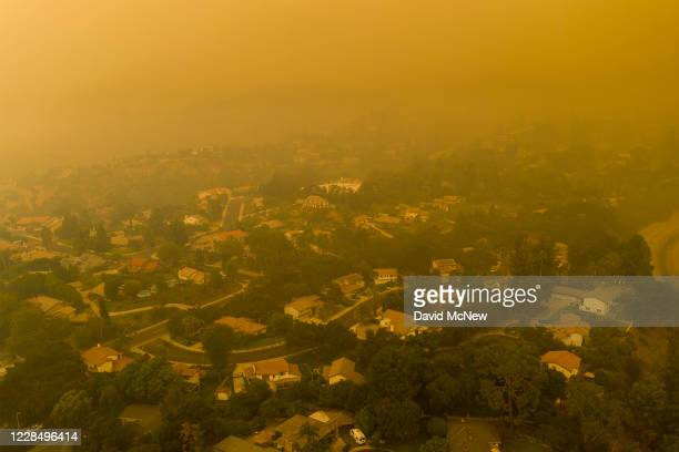An aerial view shows neighborhoods enshrouded in smoke as the Bobcat Fire advances toward foothill cities and new evacuation order go into effect on...
