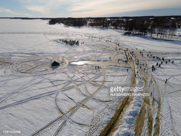 An aerial view shows paople gathered to assist the construction of the ice carousel for a world record attempt on a frozen lake in Lappajärvi,...
