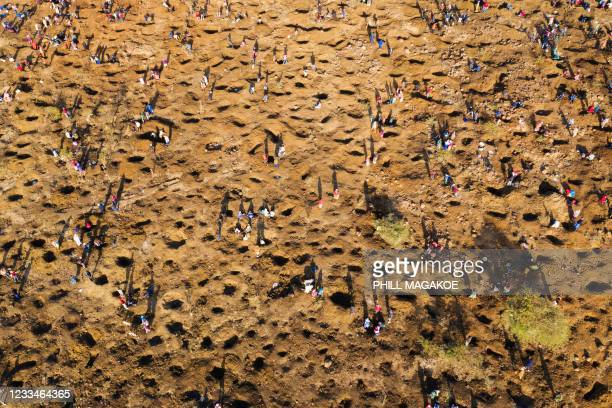 An aerial view shows people digging as they search for what they believe to be diamonds after the discovery of unidentified stones at KwaHlathi...