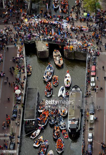 An aerial view shows people gather on boats floating on the Ij river in Amsterdam on April 30 2013 during celebrations for the abdication of Queen...